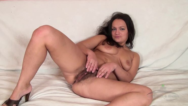 Mila fingers her dark haired pussy