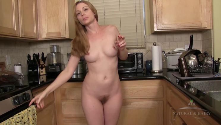 Heidi masturbates her hairy pussy in the kitchen.